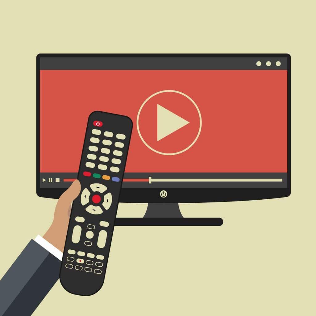 """TV mostrando um ícone de vídeo e uma mão segurando um controle remoto. A imagem faz referência ao tema """"estudar por videoaulas""""."""