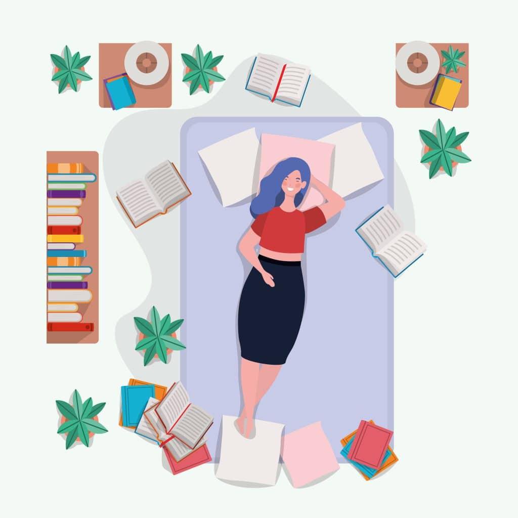 Garota deitada em uma cama sorrindo com vários livros e cadernos espalhados pelo colchão.