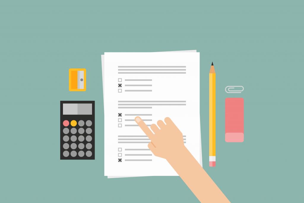 Uma prova em cima da mesa juntamente com uma calculadora, apontador, borracha e lápis. Há uma mão apontando para uma das respostas da prova.