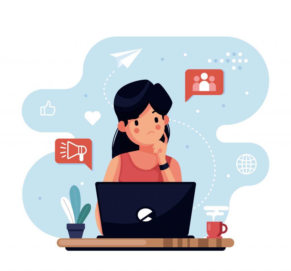 Garota sentada com expressão de pensativa. Ela tem um computador a sua frente.