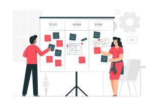 Um homem e uma mulher organizando tarefas do plano de estudos em um grande quadro.